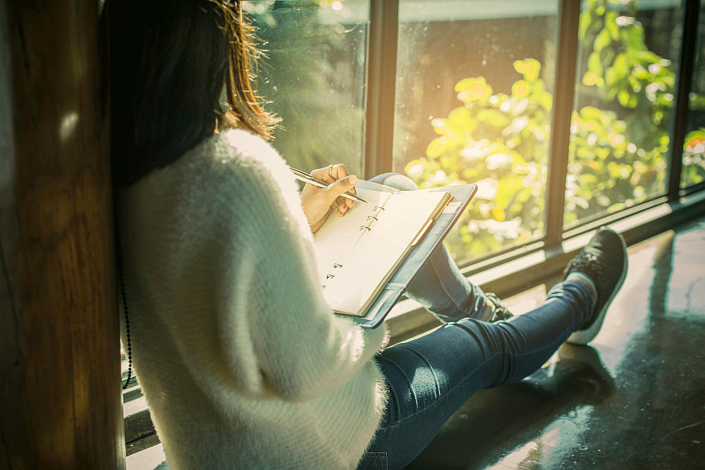 Morning scene of young hipster woman writing on notebook | Best Self-Love Books To Help Boost Your Self-Esteem | self love books | books for self love
