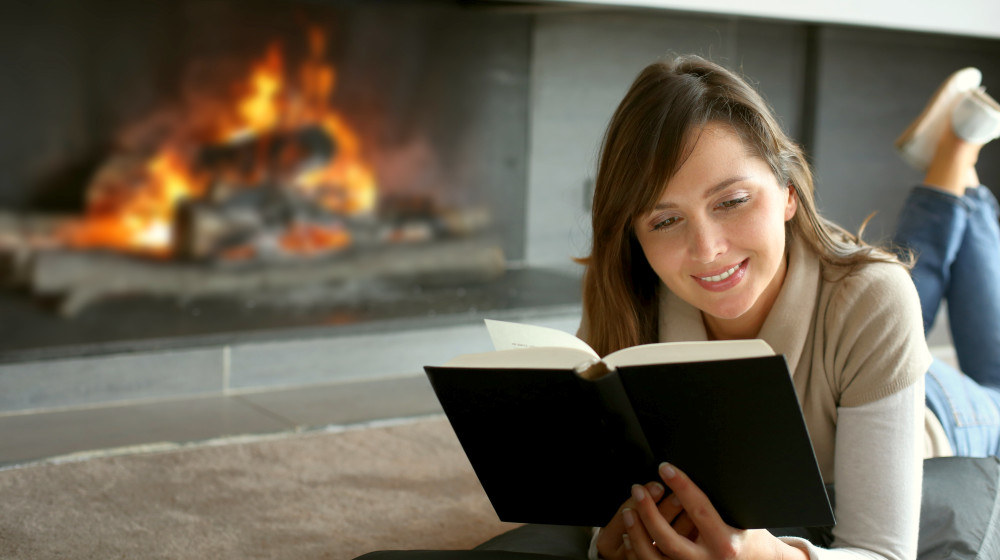 Beautiful woman reading book by fireplace | Best Self-Love Books To Help Boost Your Self-Esteem | self love books | love self help books | Featured