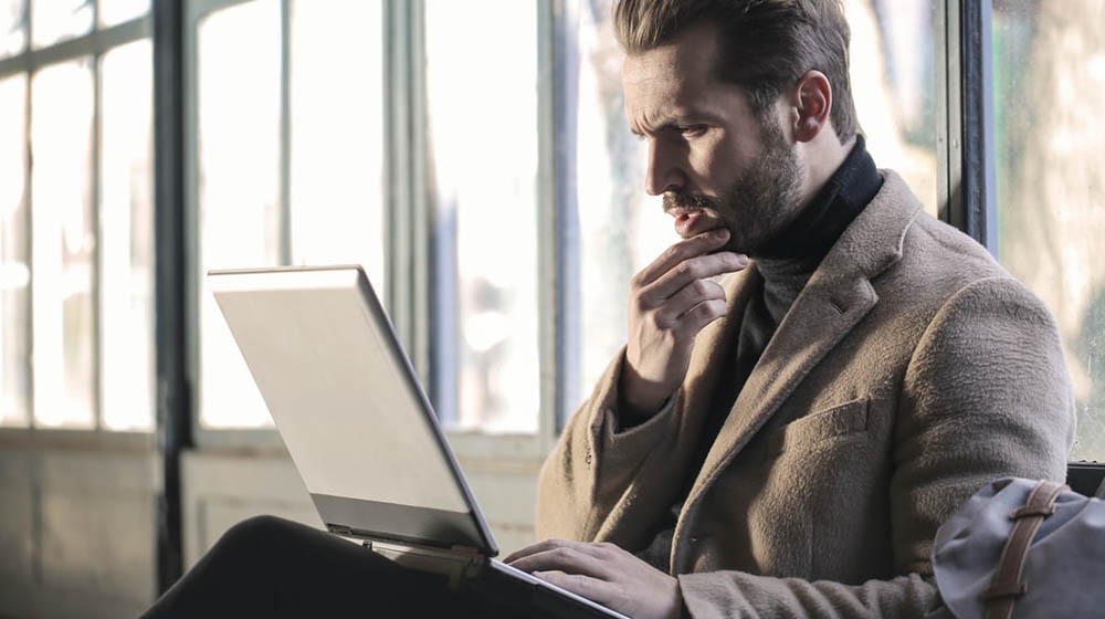 Business man in suit looking attentively at the laptop | Commit 100 To Decisions