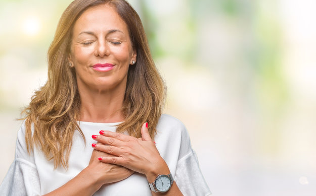 Happy middle-age woman in a white tshirt holding her chest | Heart Health