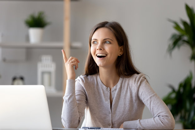 Young smiling woman in white clothes pointing and looking at the ceiling infront of her laptop | Improved Understanding