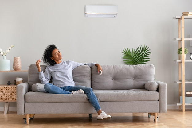 A black woman chilling on her sofa and holding the AC remote control | Mood Improvement