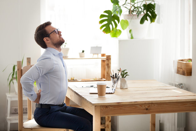 Middle-age man in white t shirt and black pants having a backache | Physical Pain Relief