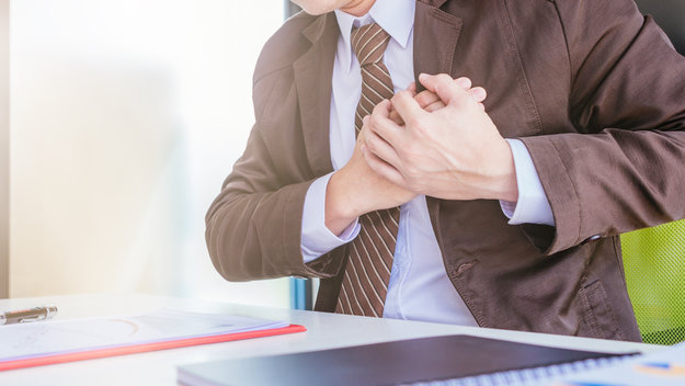 A man in his suilt and tie holding his hands before his chest in an office | 10 Uses and Benefits of Mindfulness-Based Stress Reduction