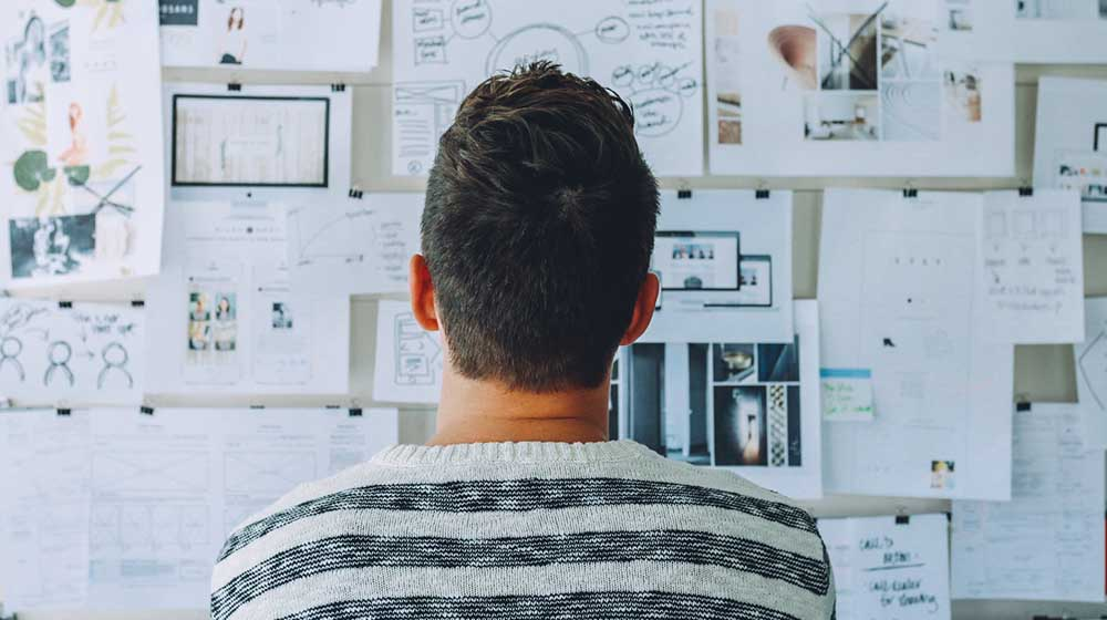A young man looking at the wall full of notes   Feature image   7 easy ways to get better at strategic thinking