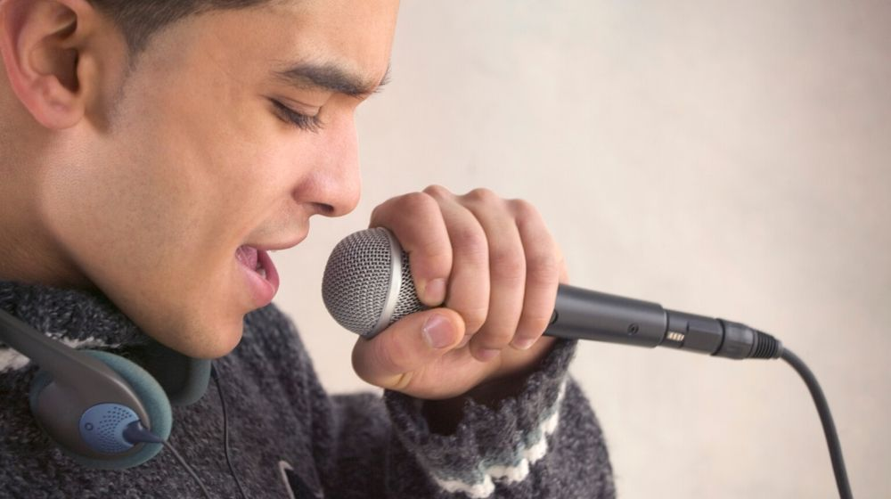 A young man with a headphone around the neck is holding a micro singing | feature