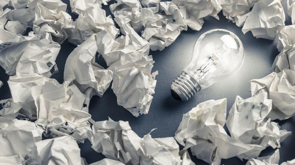 Glowing light bulb among the crumpled rubbish paper, idea from mistake concept | Feature Image | How to Learn From Your Mistakes In 5 Actionable Ways