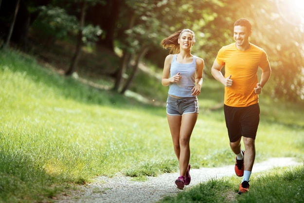 A couple jogging and running in a park | Living Healthy