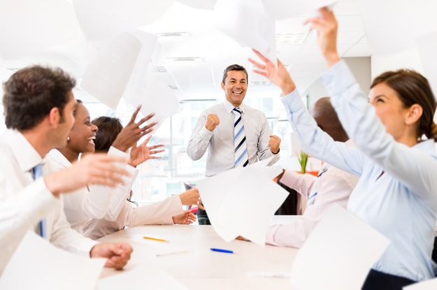 A leader in a room full of cheerful employees | The function of leadership is to produce more leaders, not more followers