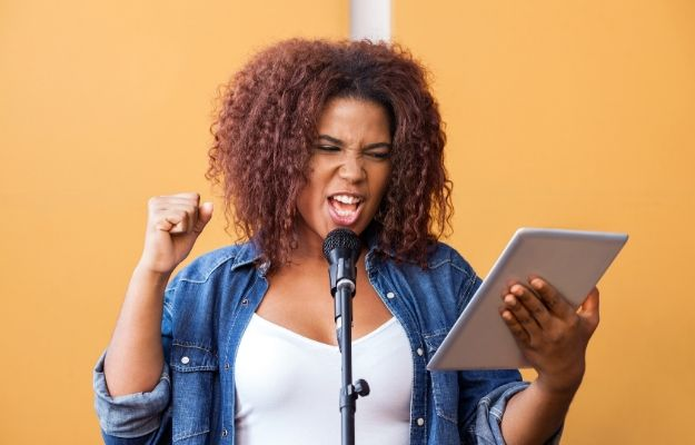 a black woman holding a tablet is singing with micro | Hitting High Notes Safely