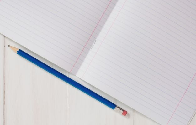 a blue pencil next to a lined-paper notebook | Get Lined Paper