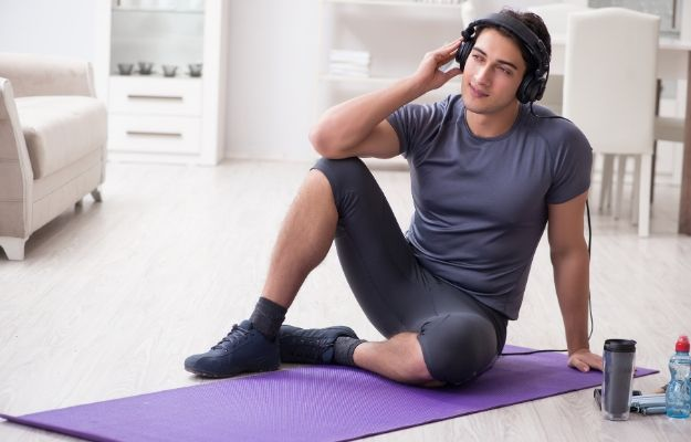 a man is listening to music while doing exercises | 12 Motivational Songs For Working Out