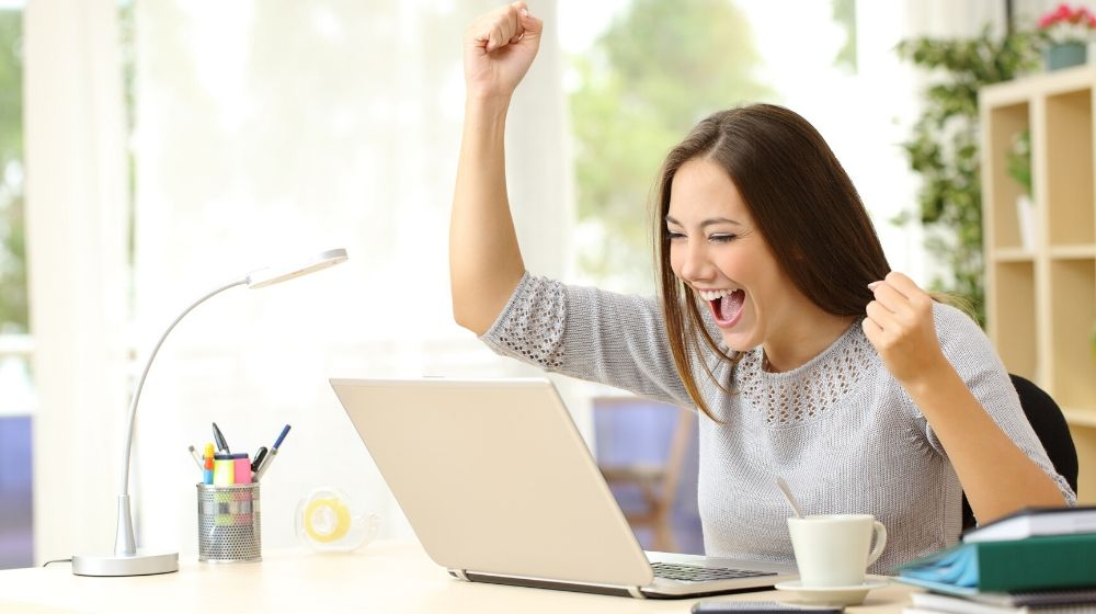 a woman get extremely excited looking at the computer screen | feature image