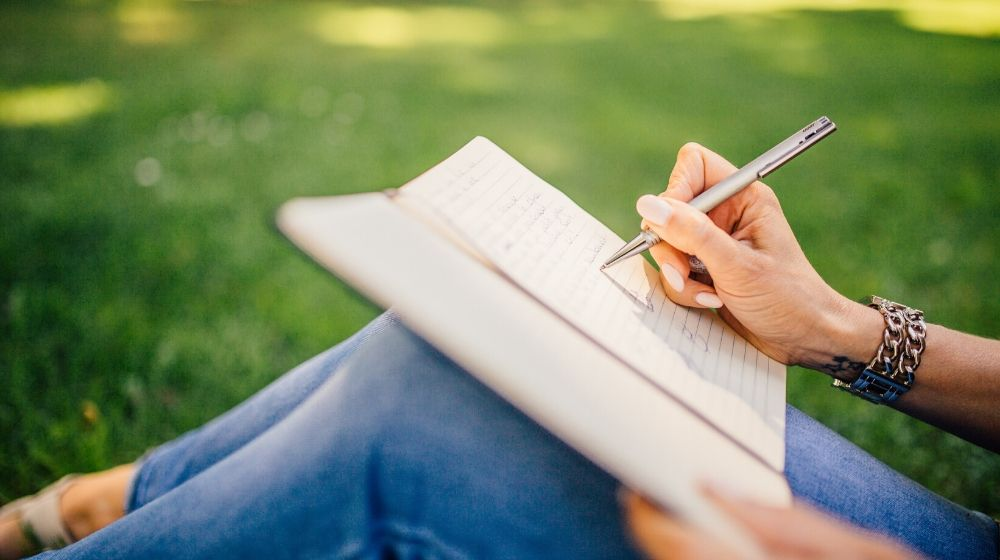a woman sitting on the grass writing on her notebook with a pen | feature image