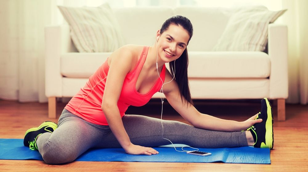 a young woman doing exercises at home listening to music | feature