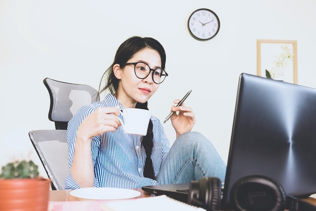 asian woman with glasses working on her computer thinking with a cup and a pen | Evaluate Your Work Often+