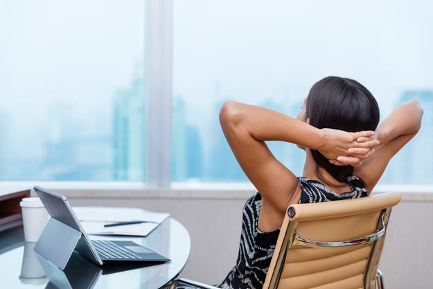 tanned woman in an office chair having a break at work | Take Regular Breaks