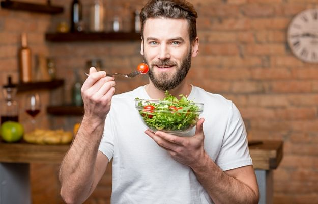 Handsome bearded man in white t-shirt eating salad in the kitchen | eat right | 7 Ways To Invest In Yourself This Year (And Why It Matters)