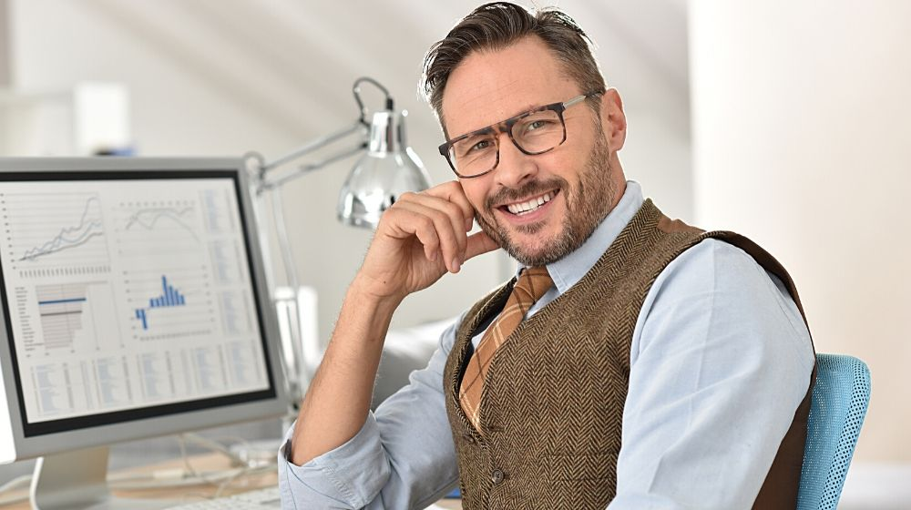 Middle-aged businessman with eyeglasses in office | a senior man doing paper work with calculator and computer | Feature img | How To Start Over at 50 With No Money