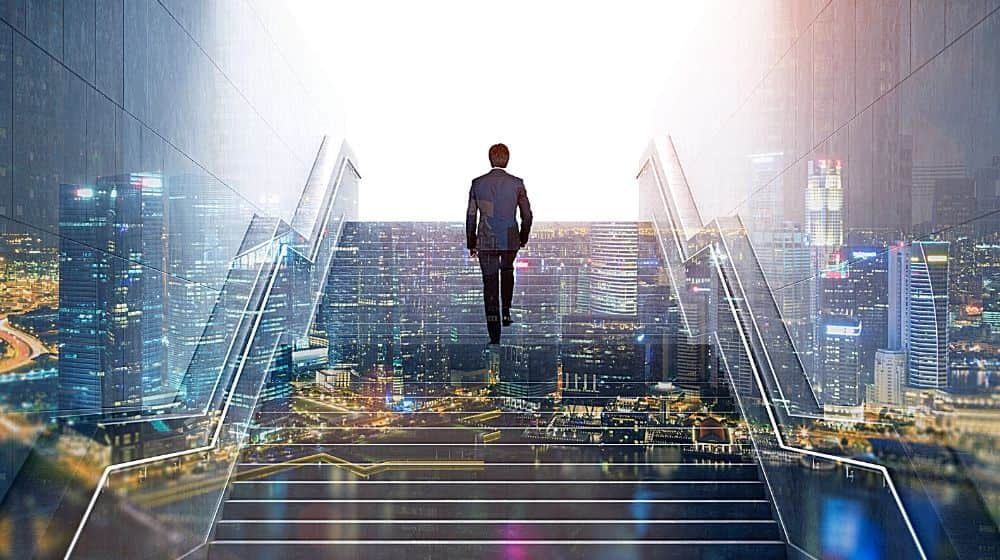 Rear view of a businessman climbing stairs to get to a large city center | Feature img | 9 Principles That Will Pave Your Road To Success