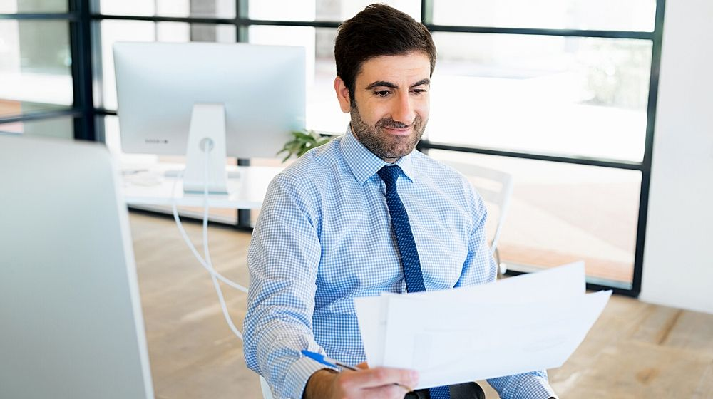 Young businessman in office sitting and smiling | Feature | How To Assert Yourself: 9 Tips To Be More Assertive