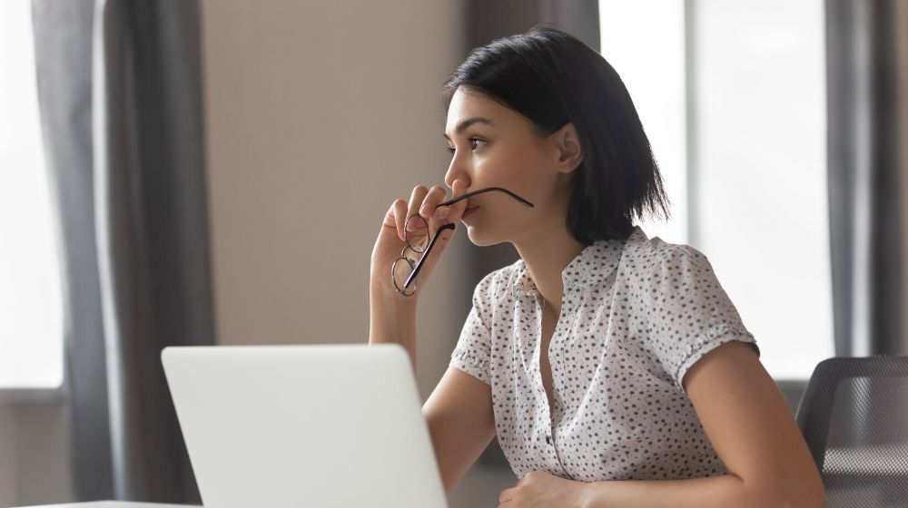 business woman looking away thinking solving problem at work | Feature | 9 Ways to Boost Moral Integrity (And What That Means)