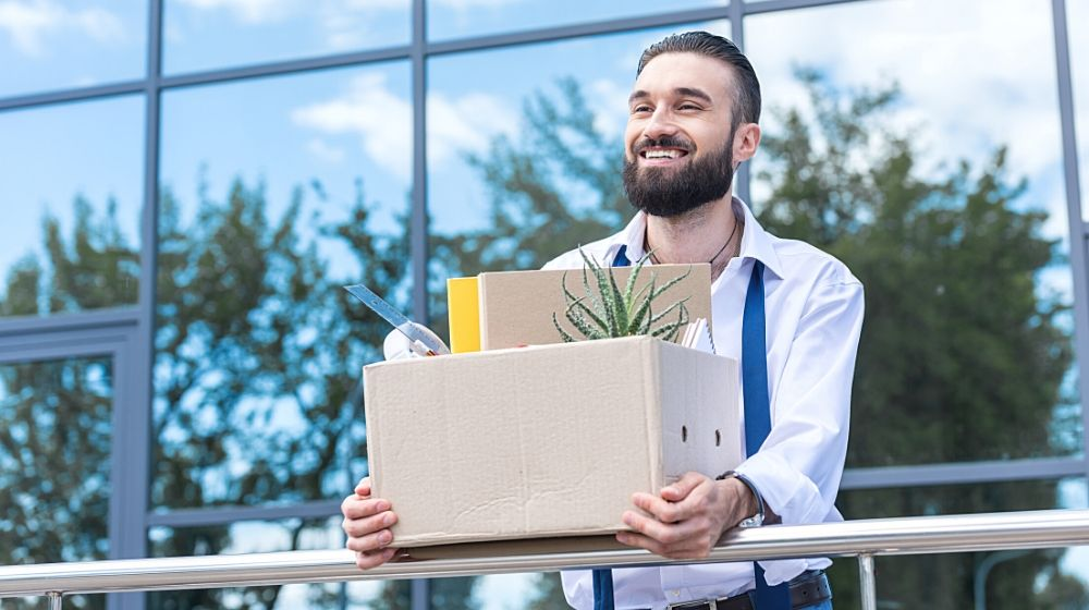 happy businessman with cardboard box with office supplies in hands | Feature | Is It Better To Quit Or Be Fired?