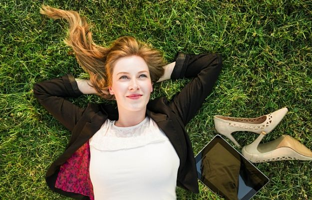 """young independent woman relaxing on grass in park 