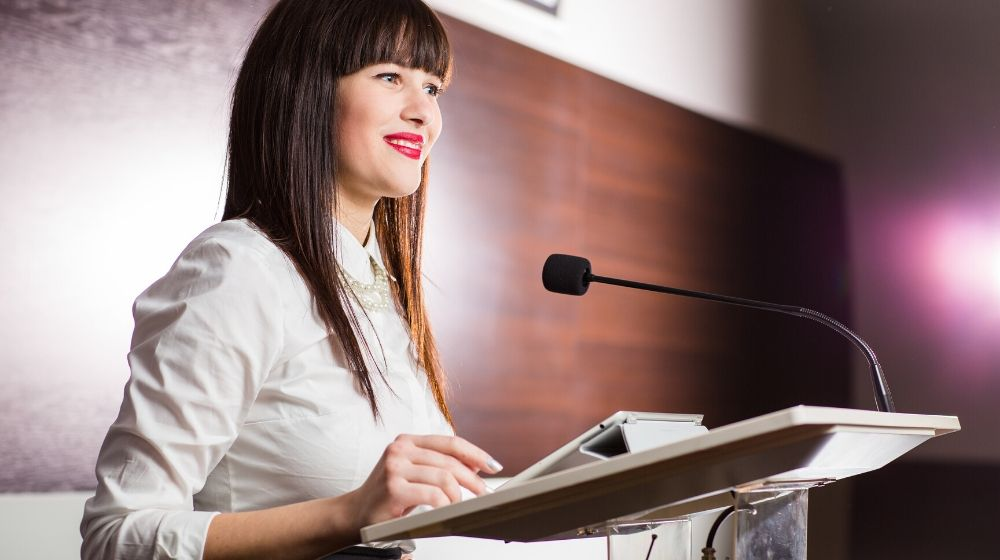 A young business woman giving a presentation in a conference | Feature | How Motivational Speakers Nail Their Speeches: 8 Tips