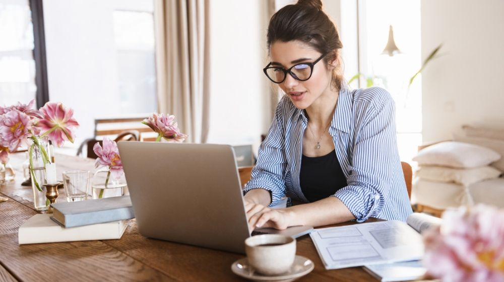 A young woman working from home next to the cup of coffee | Feature | How To Work From Home Effectively