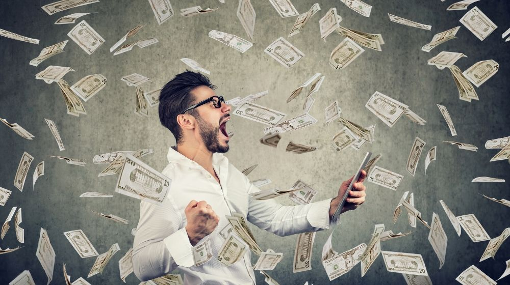 white shirt man holding phone surrounded by money | Feature | 5 Short Term Investments Made Easy