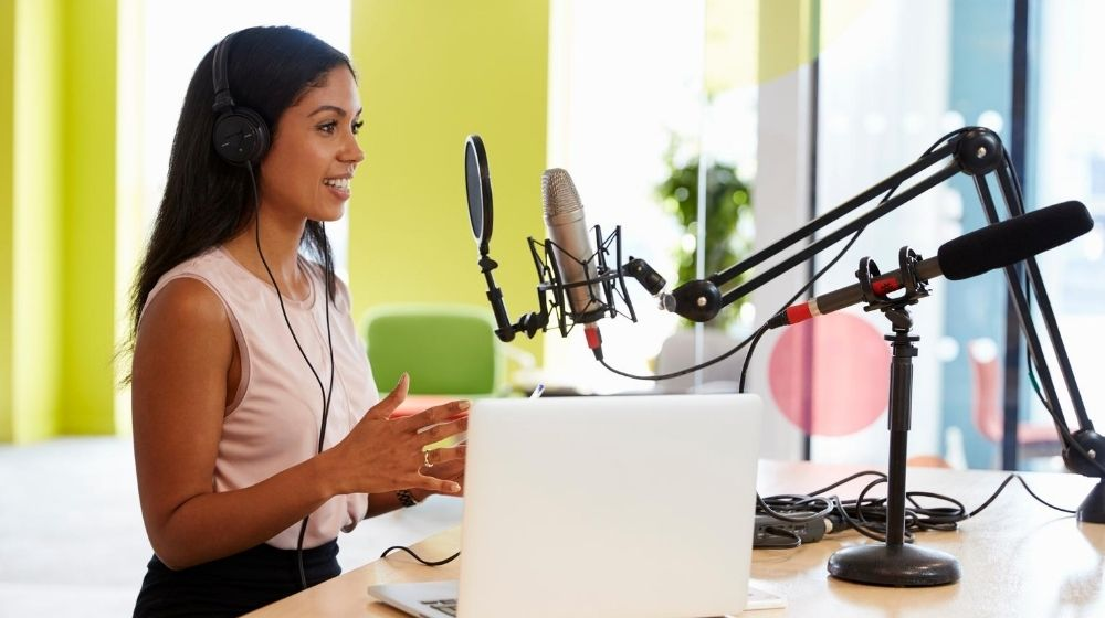 A girl is doing podcast, sitting in front of the mic | Feature | 6 Tips to Become A Real Altruist