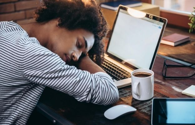 A man taking a nap with the laptop and coffee on the desk | Nap | How Break Time Can Improve Your Performance at Work