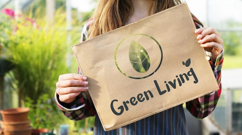 a girl is showing a board with the line 'green living' | Feature | How Sustainable Living Can Lead to Your Best Life