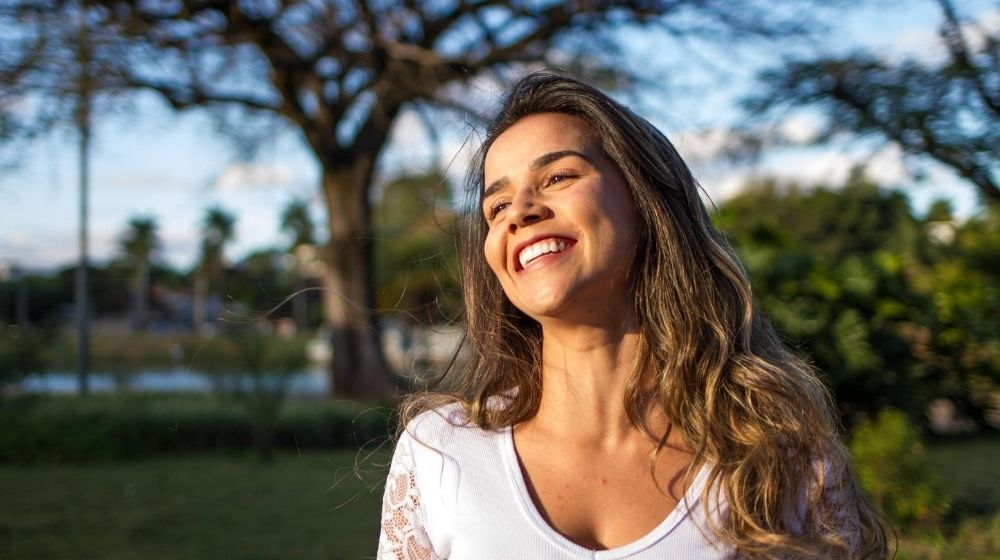 a girl smiling showing her happiness and peace | Feature | How to Be a Soothing Presence: 11 Tips