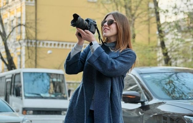 a girl wearing coat and holding camera with 2 cars behind | Pick One Subject | Be A Better Photographer I 9 Tips To Take Better Pictures