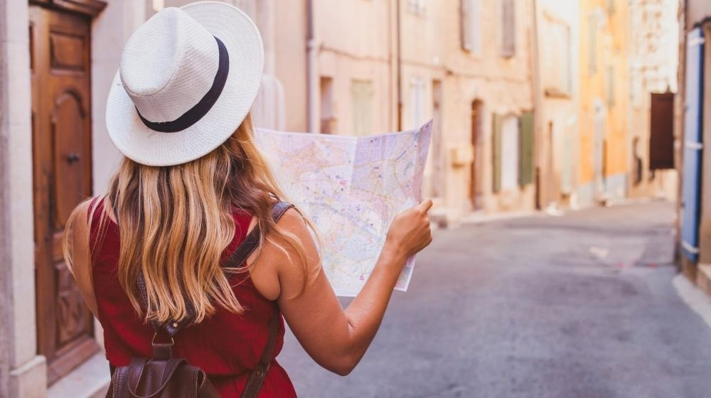a girl wearing white hat and holding a mind to find a way | Feature | Travel For Less With These 9 Tips
