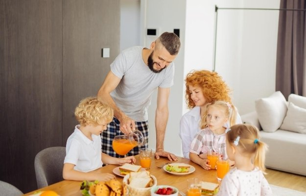a man is pouring orange juice for his family | Love Your Family | How to Be a Better Man in 13 Ways