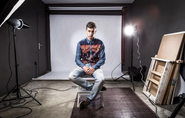 a man sitting in the middle of the studio and 2 flashes spotlight | Understand Flash and ISO | Be A Better Photographer I 9 Tips To Take Better Pictures