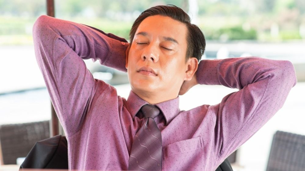 a man wearing purple shirt taking a break on chair | Feature | How Break Time Can Improve Your Performance at Work