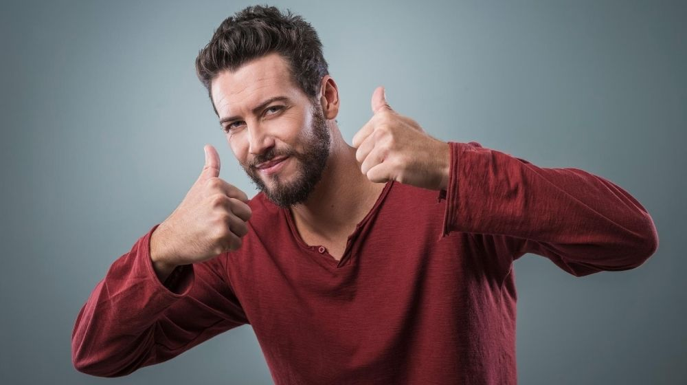 a man wearing red sweater shows a thumb up | feature | How to Be a Better Man in 13 Ways