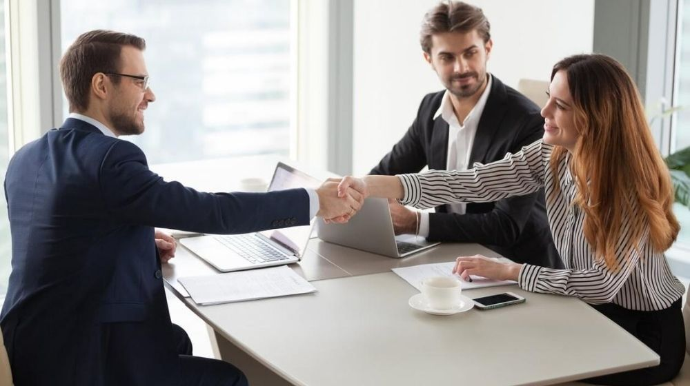 group of staff negotiating and shaking their hand | Feature | How to Persuade People: 9 Tips from Salespeople