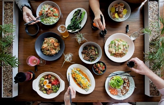 hands of friends on asian dinner table   Asian Cooking   How to Travel Via Your Dinner Plate