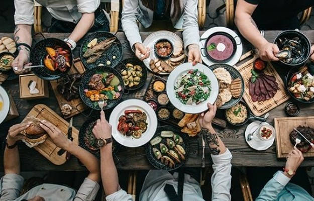 hands of friends on south american dinner table   South American Cooking   How to Travel Via Your Dinner Plate