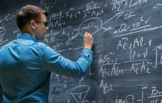 Young guy writing Mathematical Formula on a Big Blackboard | How To Get Better At Math | Comprehend the Underlying Logic