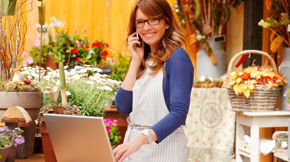 a girl is having a phone call and using laptop surrounded by flowers | Feature | 11 Better Digital Marketing Tips For Small Businesses