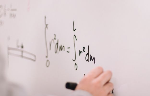 a hand writing an equation on the white board | How To Get Better At MathHow To Get Better At Math | Enjoy Your Equations