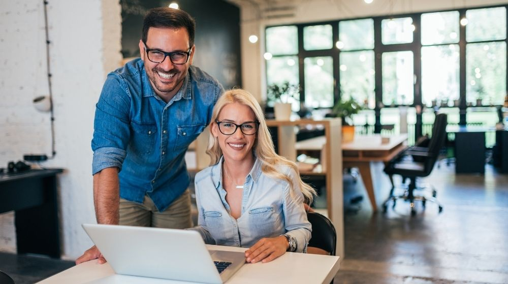a man and woman are happy doing on the laptop | Entrepreneur Ideas To Start A Business | Feature