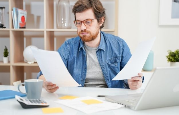 a man holding papers   Pay Off Any Debt   How to Plan for A Happy Retirement in Your 30's