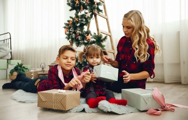 a woman giving gifts to 2 children on Christmas | Get Gift-Giving Help from Other Kids​ | 10 Ways To Become The Cool Aunt or Uncle
